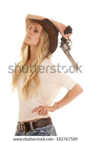 a woman looking up while holding onto a pistol. - stock photo