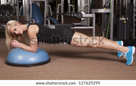 A woman looking while doing plank in a gym on a half ball.