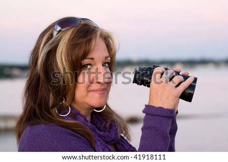 A woman looking with binoculars at the beach. - stock photo