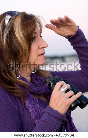 A woman looks at something off in the distance with binoculars in her hands while at the seashore. - stock photo