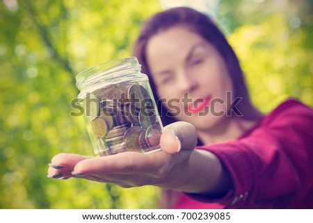A woman looks with one eye on a glass jar with money