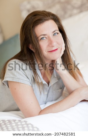A woman lying at the end of the bed - stock photo