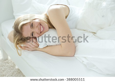 A woman lying at the end of the bed underneath the quilt and smiling - stock photo