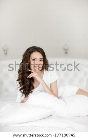 A woman lying at the end of the bed underneath the quilt and smiling, with her head resting upon her hand with the other in her hair. - stock photo