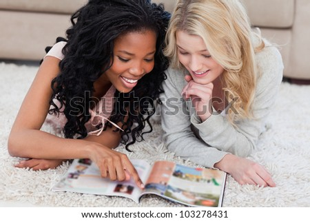 A woman lying on the floor is pointing at a magazine with her friend lying beside her