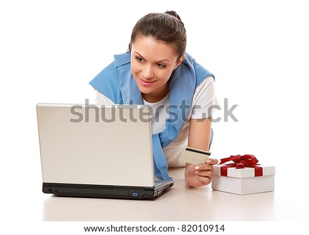 A woman lying on the floor with a credit card, present and a laptop, isolated on white