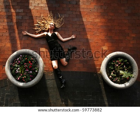 a woman lying on the ground - stock photo
