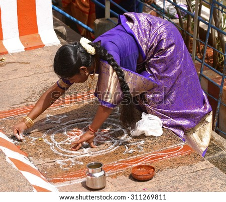 A woman makes a drawing to powders (called kalam) in the floor of the temple Meenakshi in Madurai, in the state of Tamil Nadu, India, during a pilgrimage in August 2005 - stock photo