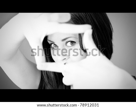 A woman making a frame with her fingers in widescreen movie format in black and white. - stock photo
