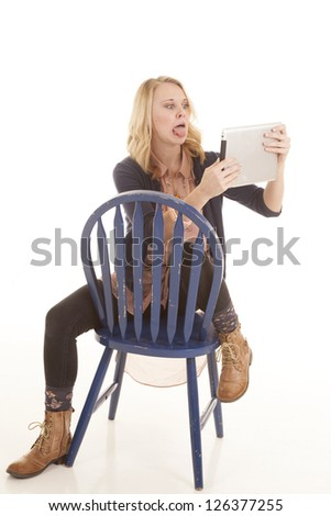 a woman making a funny face on her electronic tablet while sitting in a blue chair. - stock photo