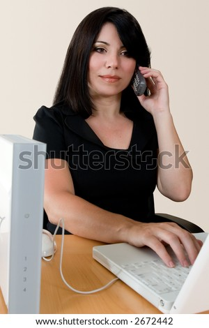 A woman making a wireless internet phone call via a wirless modem router. - stock photo