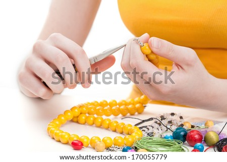 A woman making a yellow wooden bead necklace - stock photo