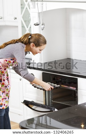 A woman making / baking muffins in white modern kitchen.
