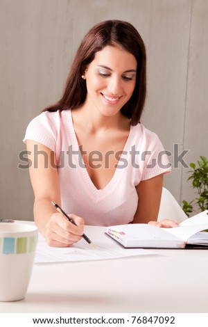 A woman making business plans sitting at a desk - stock photo
