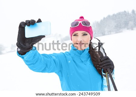 A woman making selfie by cross-country skiing in the Alps - stock photo