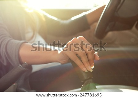 a woman manually shifting the car transmission - stock photo