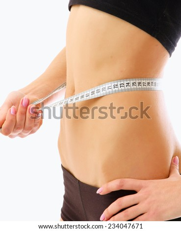 A woman measuring her waist - stock photo