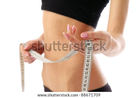 A woman measuring her waist, focus on her hand isolated on white background - stock photo