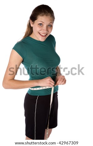 A woman measuring her waist with a happy expression on her face. - stock photo