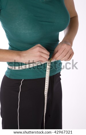 A woman measuring her waist with a measuring tape to see her size.