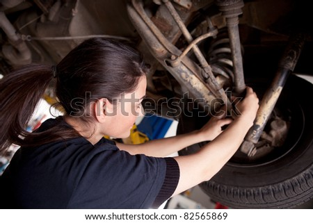 A woman mechanic working on a car, checking a cv boot - stock photo