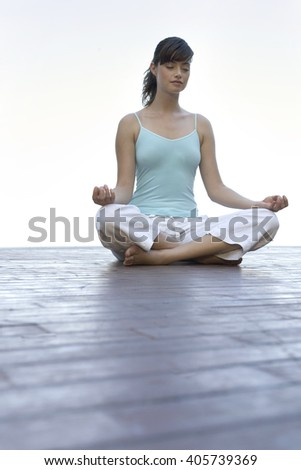 A woman meditating by a pool - stock photo