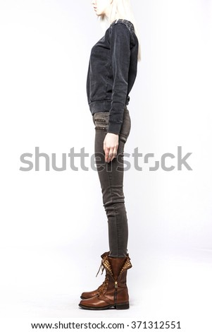 A woman(model, girl, female) stand up wearing brown denim(jeans, pants, trousers), black shirts, brown leather boots isolated white at the studio.