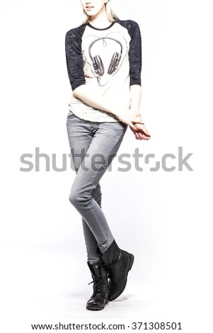 A woman(model, girl, female) stand up wearing white shirts with head phone graphic, blue denim(jeans, pants, trousers), black leather military boots isolated white at the studio. - stock photo