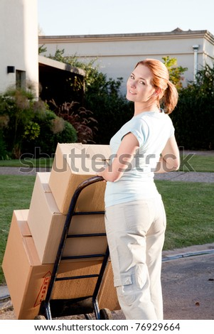A woman moving with a stack of cardboard boxes on a trolly - stock photo