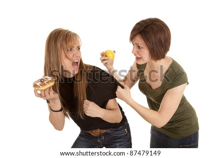 A woman not wanting her apple but wants the other womans doughnut. - stock photo
