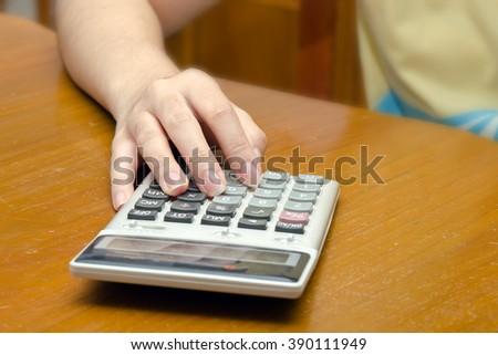A woman notes and calculates number on the note card with calculator in background - stock photo
