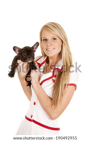 A woman nurse with a small dog holding it close to her. - stock photo