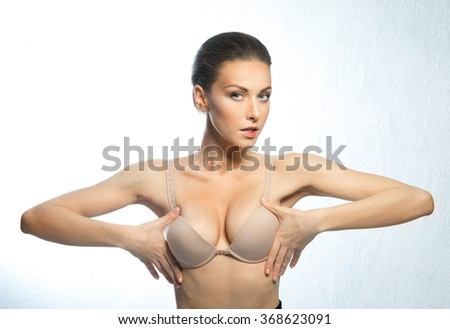 A woman of European appearance with a beautiful, large breasts, happy after plastic surgery. - stock photo