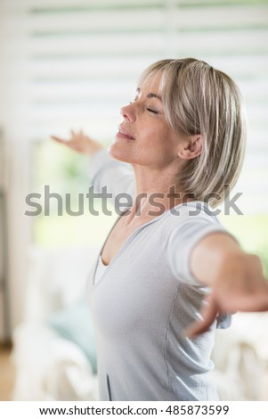 a woman of 50 years with grey hairs. she is smiling, she blossomed. she wants to stay in shape. she does yoga at home with a sports outfit. her eyes are closed