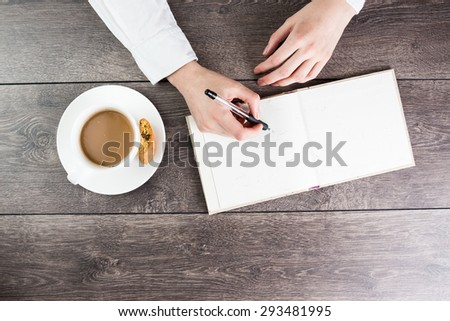 A woman office worker hands writing on empty(blank) book(note, diary) spread mockup, top view, studio. cup of cappuccino break. Empty space in notebook for blog entries, you can place your text - stock photo