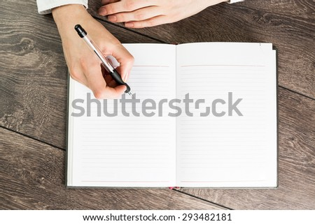 A woman office worker hands writing on empty(blank) book(note, diary) spread(unfold) mockup, top view, studio. Empty space in a notebook for blog entries, you can place your text or information. - stock photo