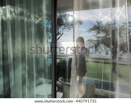 A woman on a balcony looking at the beach and sea (View through the transparent curtain)   - stock photo
