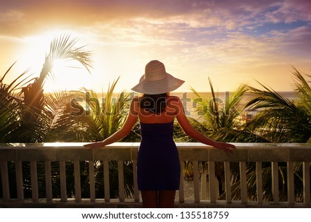 A woman on a balcony looking at the beautiful Caribbean sunset. - stock photo