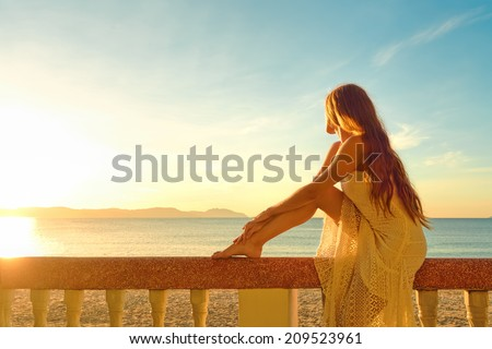 A woman on a balcony looking at the beautiful sunset - stock photo