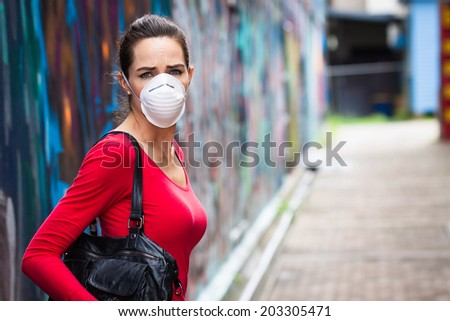 A woman on a street wearing a face mask looking upset - stock photo