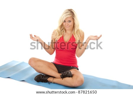 A woman on her yoga mat with a confused expression on her face. - stock photo