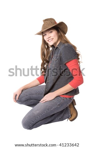 A woman on one knee smiling while wearing a cowboy hat. - stock photo