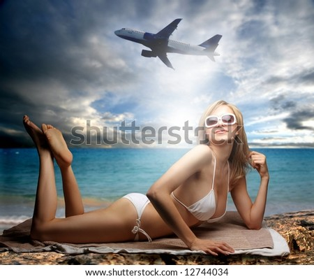 a woman on the beach and a airplane - stock photo