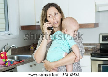 A woman on the phone while holding her baby in her arms in the kitchen - stock photo
