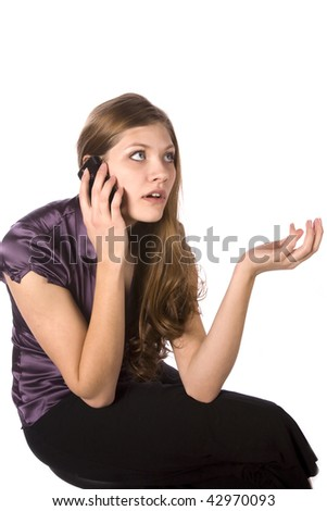 A woman on the phone with a surprised expression on her face. - stock photo