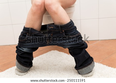 a woman on the toilet is suffering about congestion - stock photo