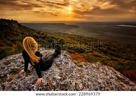 A woman on the top of a rock enjoys the view of sunset over an autumn forest - stock photo