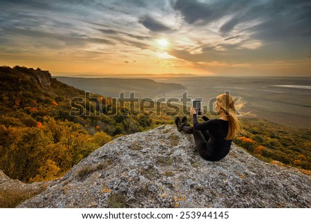 A woman on the top of a rock taking a picture using digital tablet - stock photo