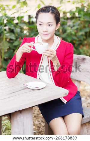 A woman on vacation, I drink coffee. Natural background. Outdoor portrait of cute blonde sitting on terrace and drinking her morning coffee.  - stock photo