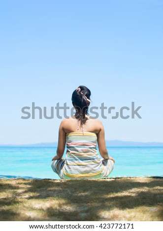 A woman on vacation sits in a yoga position and looks out to sea on an idyllic tropical beach, travel destination.